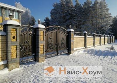 Сплошной забор из кирпича с кованными элементами