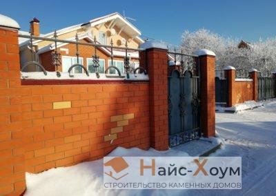 Сплошной забор из красного кирпича с кованными элементами